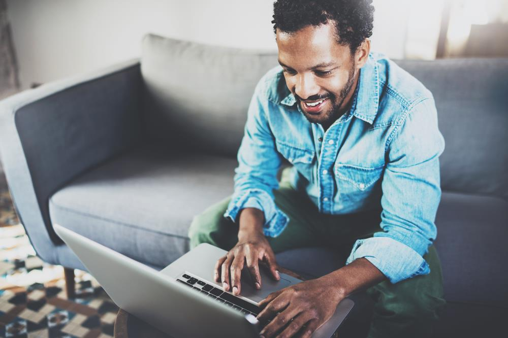 Smiling African American man sitting on couch looking at a laptop