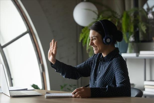 Woman waving to old colleague via video chat