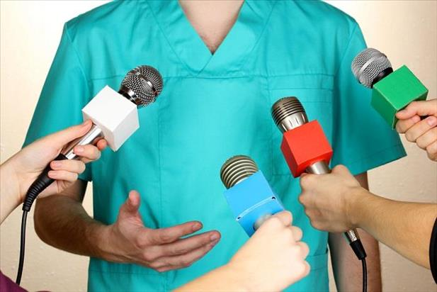 Medical professional standing in front of several microphones and answering difficult questions