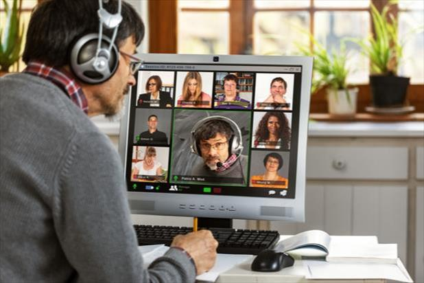 man looking at computer with virtual team on screen