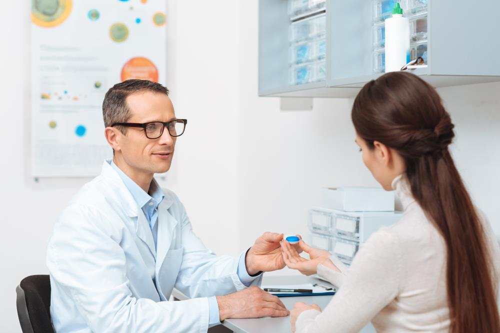 associate optometrist counseling patient on contact lens usage