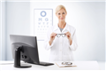 Happy hospital optometrist posing for camera with pair of eyeglasses