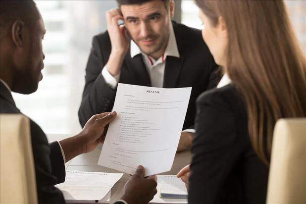 Candidate looking nervous while interviewers review his resume