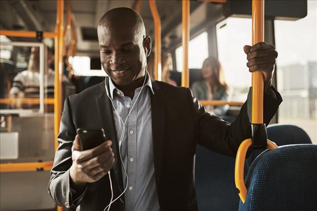 Smiling man listening to something on his phone on the bus