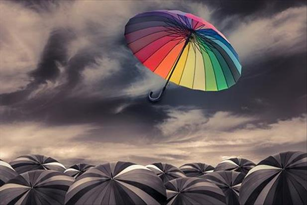 Colorful umbrella floating above group of dark colored umbrellas