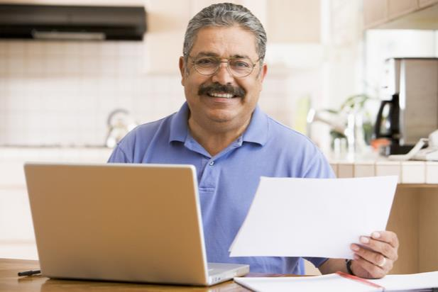 man holding up paper by computer