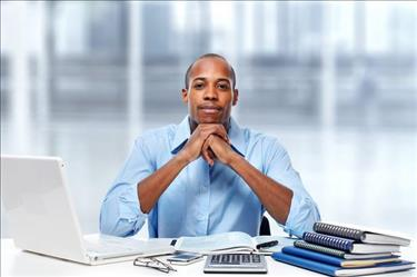 Accountant posing at desk surrounded by work materials