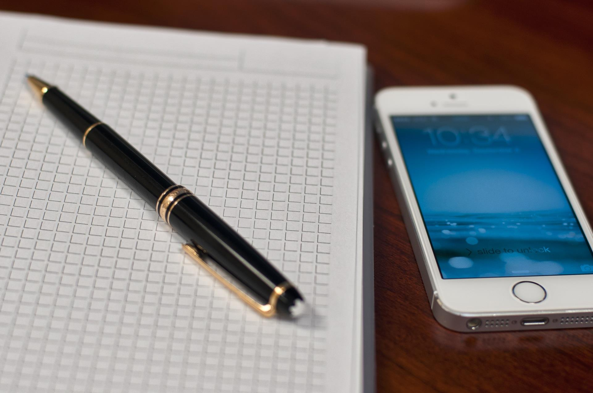 Notebook sitting next to a cell phone