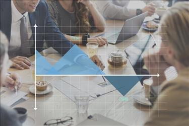 Group of professionals at conference table with graph superimposed over image