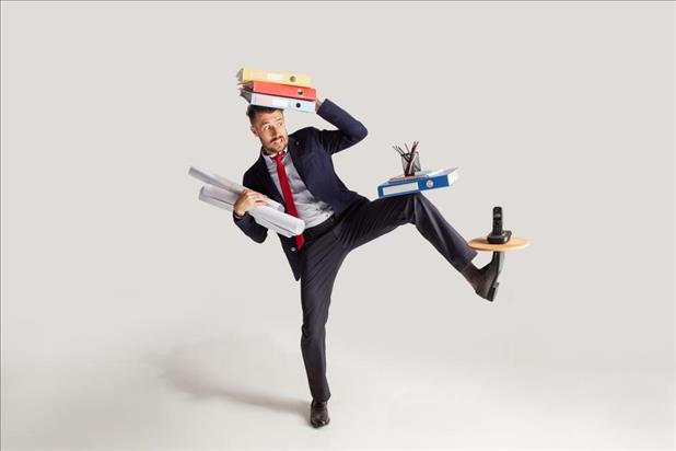 professional with multiple jobs trying to balance various items on his head, arms, knee, and foot