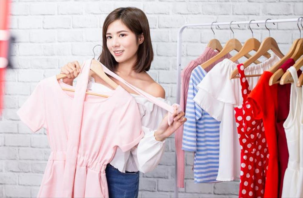 Woman looks at clothes as she decides on the outfit best suited for her backdrop