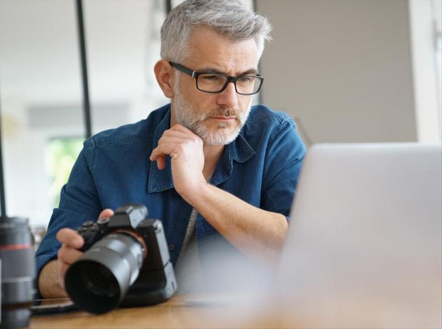 Man considers image file quality as he edits on his computer