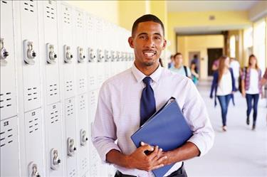 Secondary teacher standing in front of row of lockers