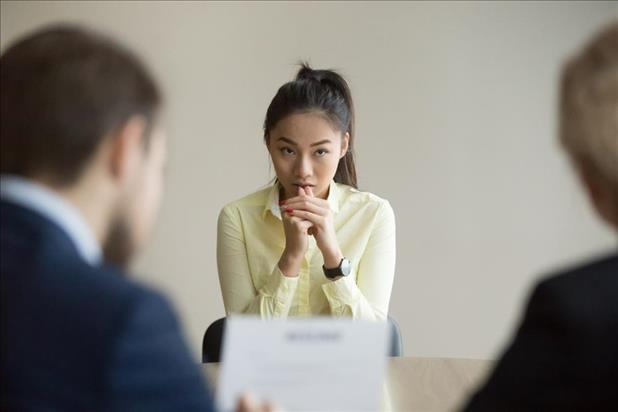 Candidate looking nervous in interview as hiring managers review her resume
