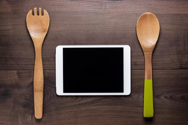 Two wooden cooking utensils on either side of a tablet