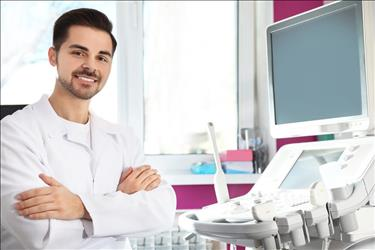 smiling diagnostic medical sonographer standing in front of his equipment in the exam room