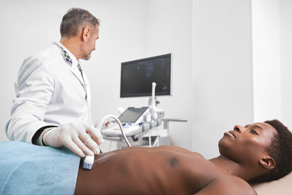 diagnostic medical sonographer performing an abdominal ultrasound exam on a patient