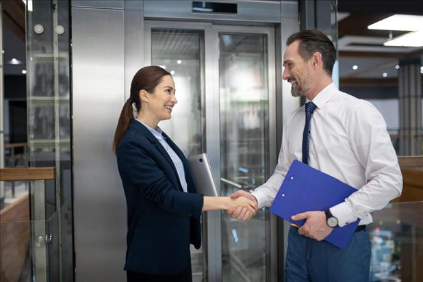 Two business people shaking hands near elevator