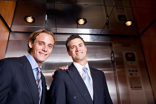 Two professionals in front of an elevator