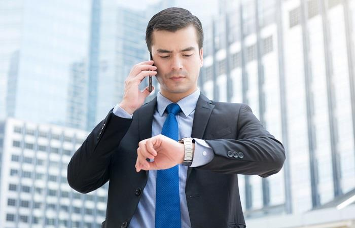 Businessman calling interviewer and looking at his watch