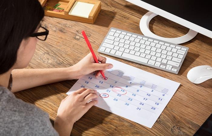 Woman circles new date on calendar in red pen