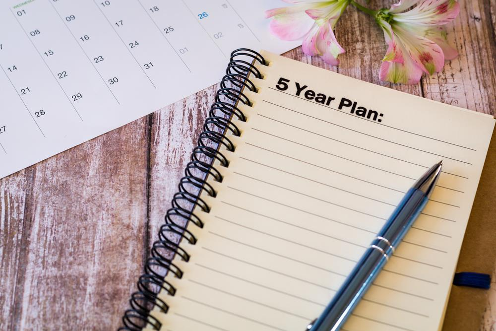 """spiral notebook with """"5 year plan"""" written at the top of the page"""