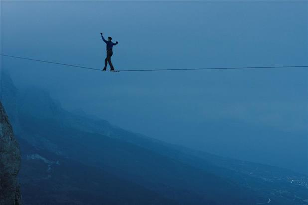 tightrope walker spanning a mountain pass at twilight