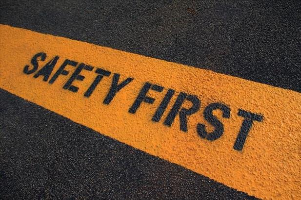"Painted line on asphalt reading ""safety first"""