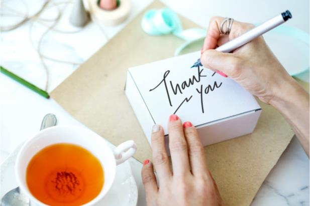 person writing a thank-you note