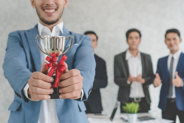 employee holding a trophy