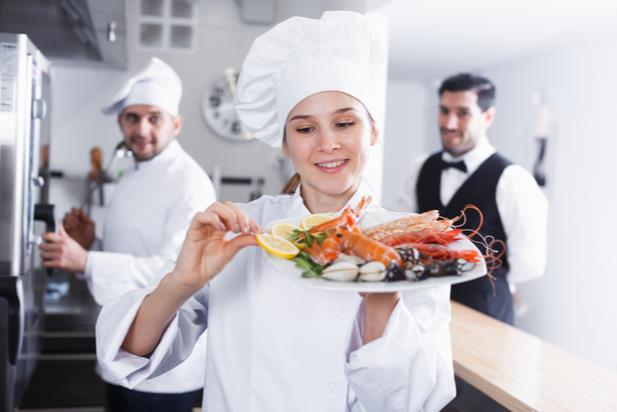 chef holding a dish with seafood