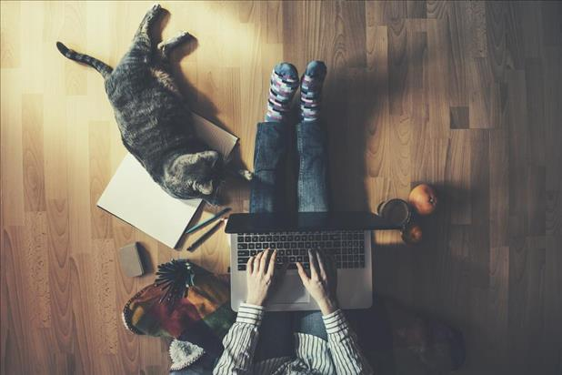 employee working from home on the floor with her laptop and cat nearby