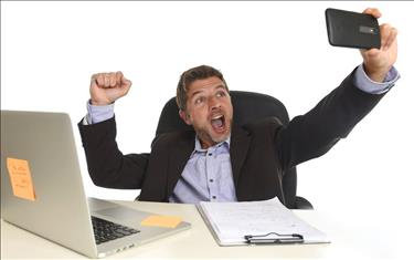Excited man taking a selfie at his desk