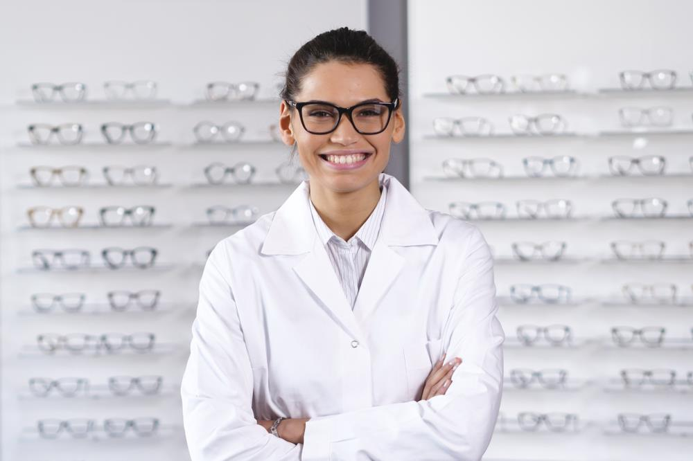 Happy optometrist posing in front of glasses on shelves