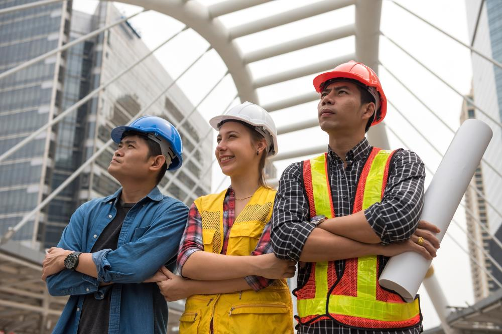 team of construction workers at a worksite looking at a building