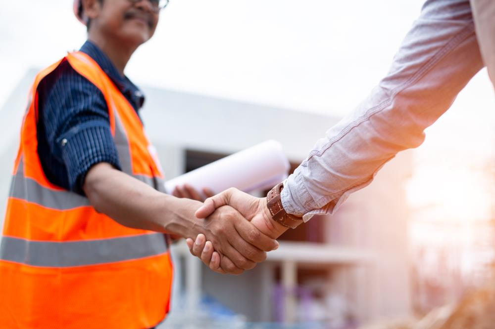 construction worker with plans in his hand shaking hands with a client