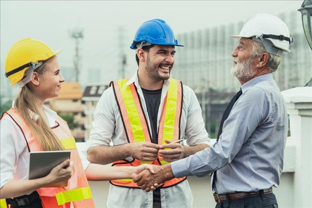 construction worker shaking a client's hand with a team member smiling at him