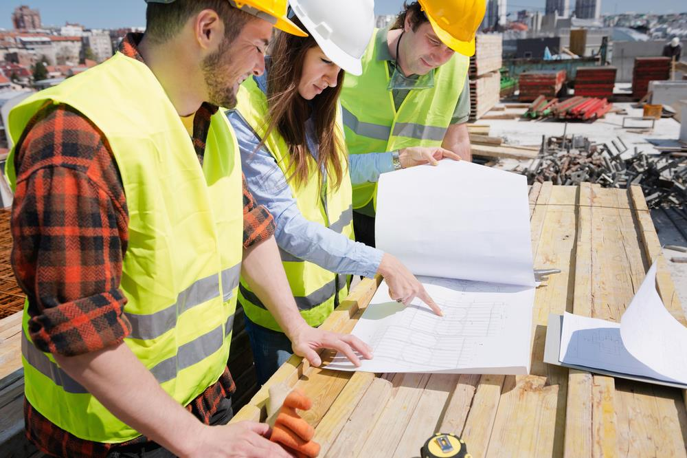 team of construction workers going over building plans