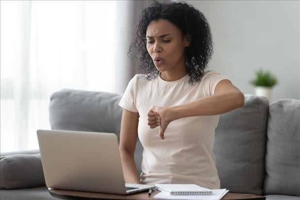 Woman putting thumbs down to something on computer