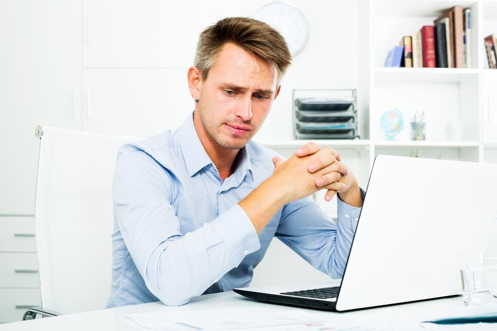 job seeker worried about his recent job loss while searching for jobs on his laptop