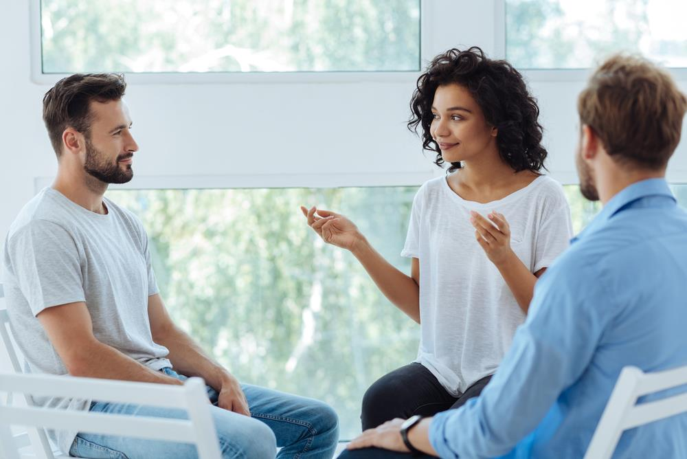 female mental health counselor holding a group session with two male clients