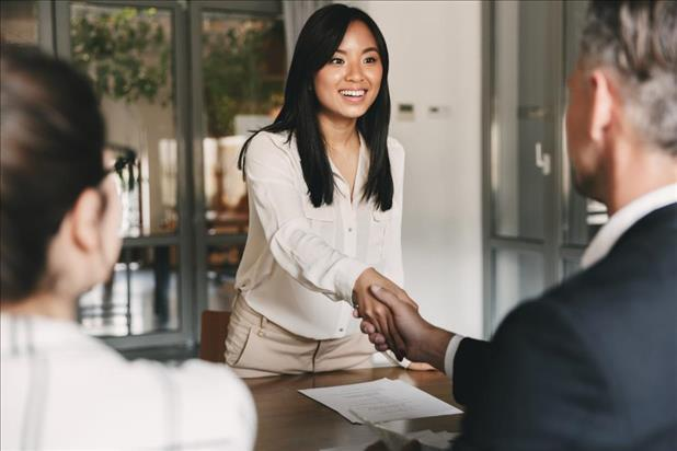 job seeker shaking hands with one of her interviewers