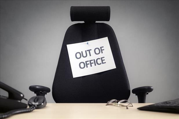 "empty office chair with ""out of office"" sign on it"