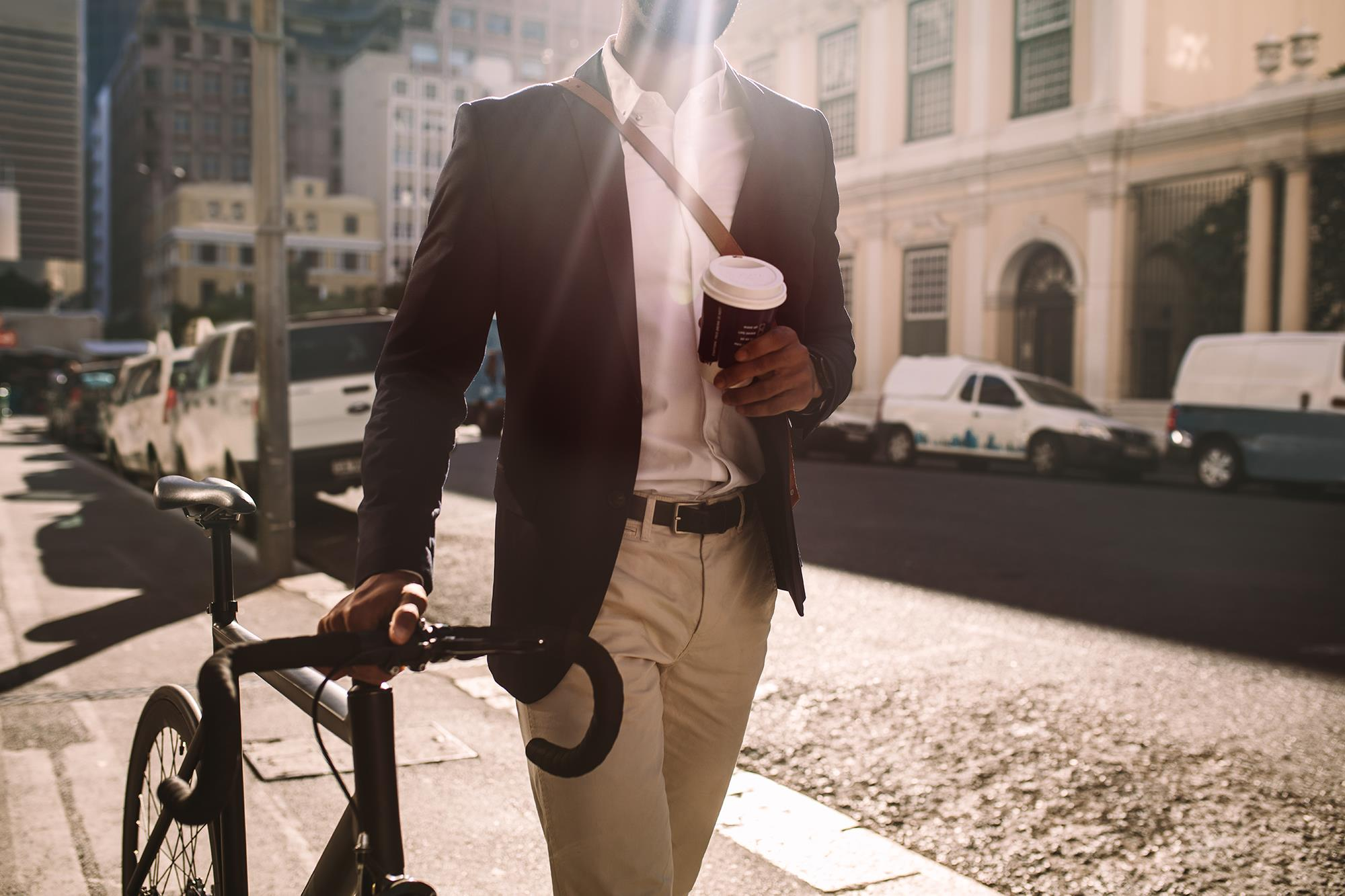 Man walking bike and drinking coffee