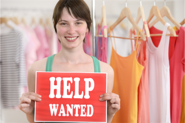 woman holding up a help wanted sign