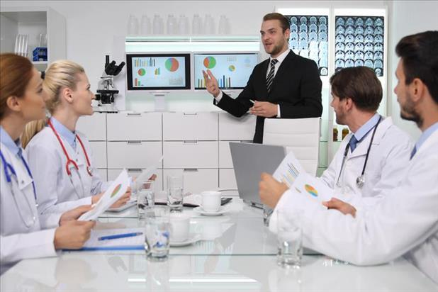healthcare administrator giving a presentation to a team of doctors