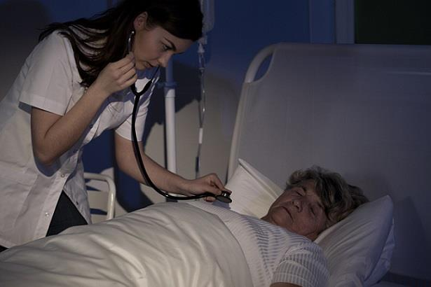 Nurse taking vitals of sleeping patient during her night shift