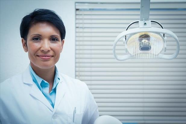 Portrait of a dentist posing in her practice