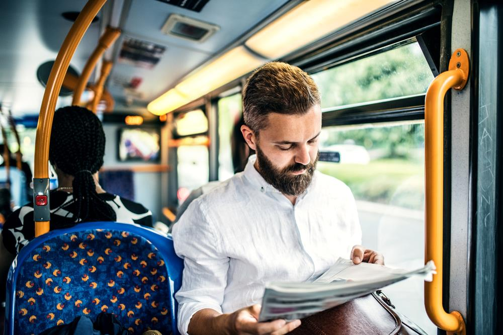 Man reading newspaper on the bus on his way to work