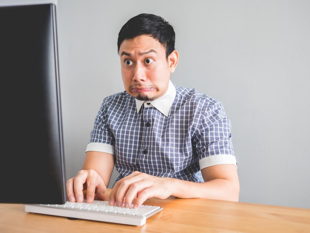 man at his computer with a shocked look on his face
